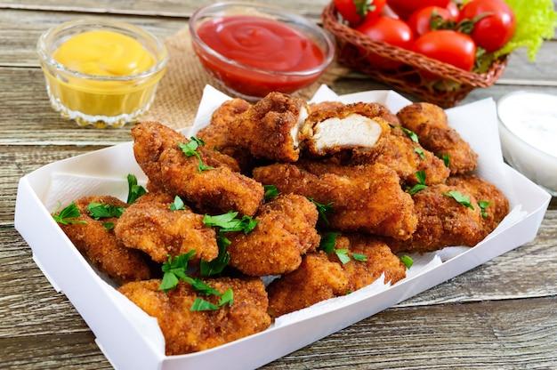 Crocchette di pollo. pezzi di carne croccante fritta, con salse diverse su un tavolo di legno. merenda tradizionale.