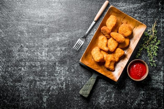 Pepite di pollo sulla piastra con forcella, salsa e timo sul tavolo rustico