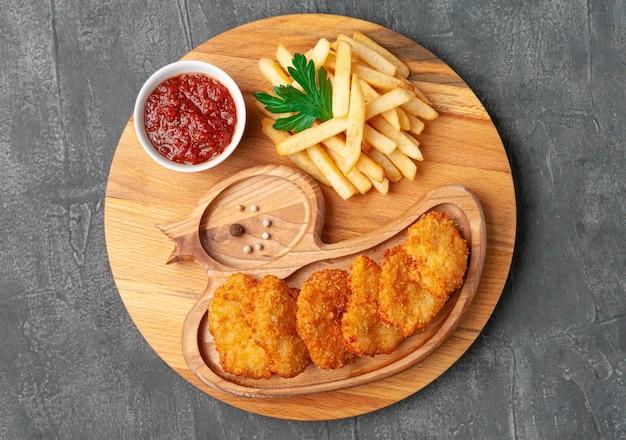 Bocconcini di pollo con patatine fritte e salsa di pomodoro. su una tavola di legno rotonda. vista dall'alto. sfondo grigio cemento.