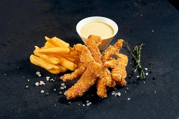 Bocconcini di pollo con patatine fritte e salsa su uno sfondo scuro.