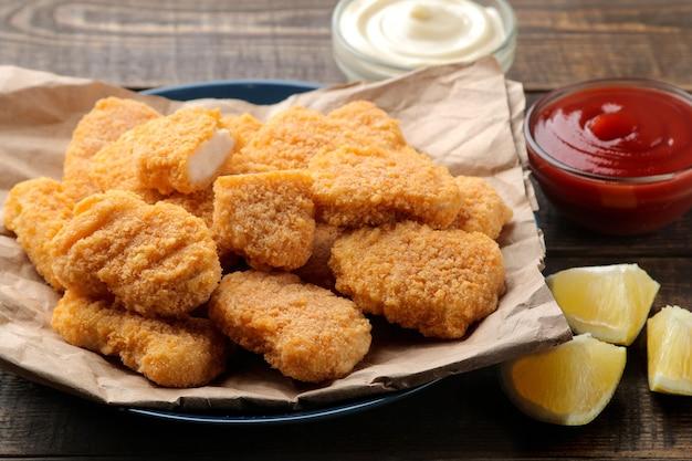 Pepite di pollo con salsa rossa e bianca su un fast food di tavolo in legno marrone