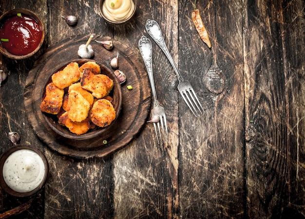 Bocconcini di pollo con salse varie. su uno sfondo di legno.