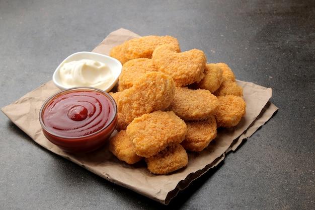 Bocconcini di pollo con salsa bianca e rossa su fondo marrone. fast food