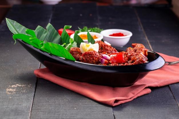 Pollo peralan o pollo al curry secco piatto di pollo speciale kerala disposto in un vasellame nero