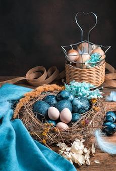 Pollo e uova di quaglia in un nido e in un cesto su fondo marrone.