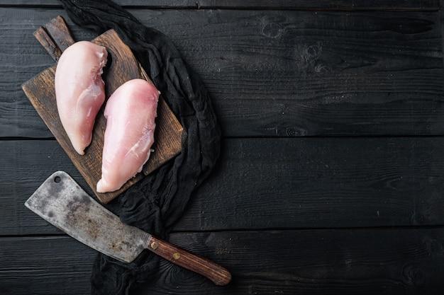Filetti di pollo crudo con coltello da macellaio sul tavolo di legno nero, piatto laici