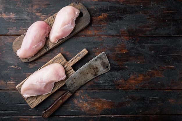 Filetti di pollo crudo con coltello da macellaio, sul tavolo di legno scuro, vista dall'alto
