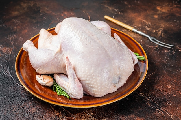 Pollo, pollame crudo in un piatto rustico con rosmarino. sfondo scuro. vista dall'alto.
