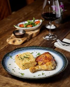Pollo e riso con insalata di verdure fresche e un bicchiere di vino rosso