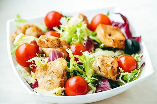 Insalata di pollo con pomodorini, lattuga e verdure per una dieta sana, servizio di consegna di cibo e concetto di ordine online