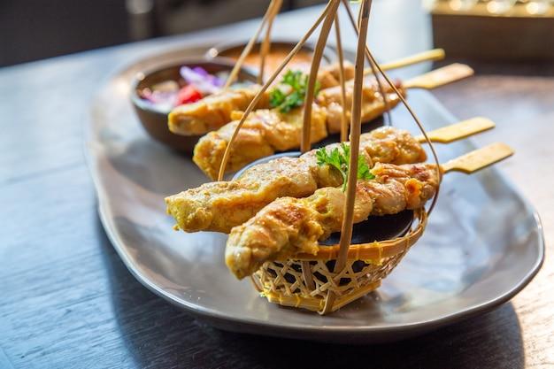 Chicken satay o chicken kebab sulla piastra con contorni e salsa thailandese.