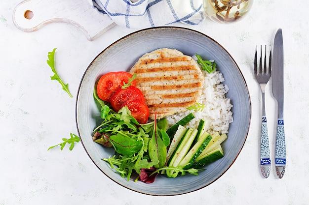 Cotoletta o cotoletta di pollo, carne di pollame alla griglia e riso bianco bollito con insalata fresca