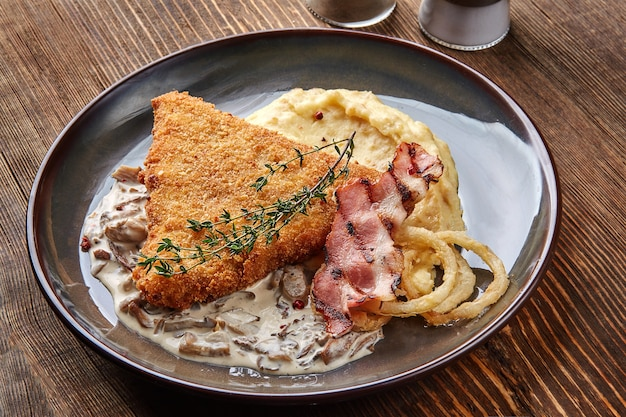 Cotoletta di pollo con purè di patate alle erbe e salsa di funghi su piatto su sfondo di tavolo in legno ...