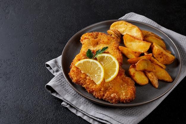Cotoletta di pollo con patate idaho su un piatto scuro