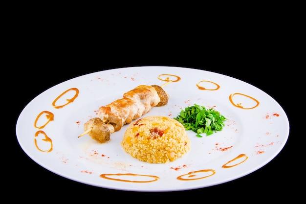 Spiedino di pollo: filetto di pollo, peperone, funghi, cous cous piccante con verdure e pomodori secchi con prezzemolo.