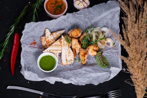 Spiedini di pollo con burro verde e pita alla griglia su una superficie scura