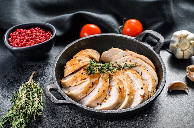 Filetto di petto di pollo a fette in padella. bistecca alla griglia. sfondo nero. vista dall'alto.