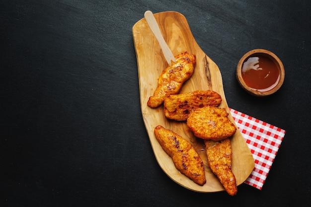 Pezzi di petto di pollo spuntino con salsa fast food sulla piastra.