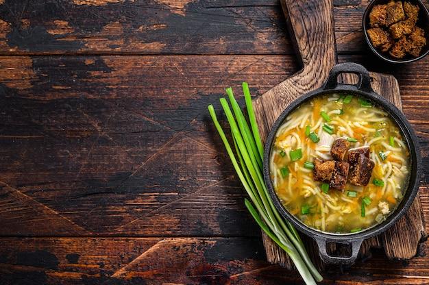 Zuppa di pollo con noodles e verdure. fondo in legno scuro. vista dall'alto. copia spazio.