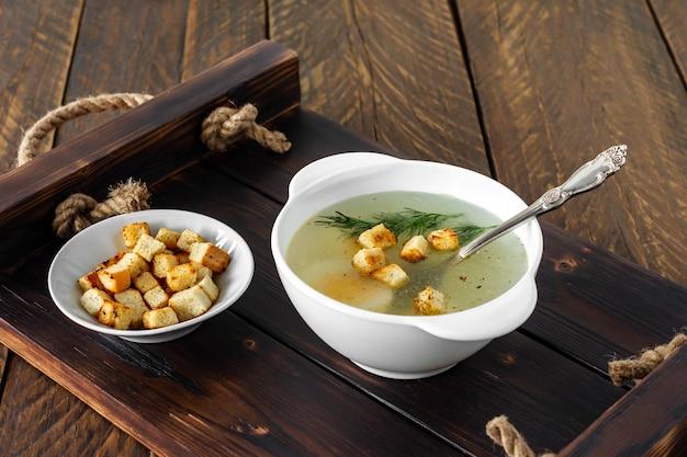 Zuppa di pollo con verdure in ciotola bianca. brodo casalingo saporito su un fondo di legno.