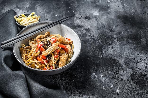 Pollo saltato in padella. tagliatelle di udon wok. cibo asiatico tradizionale. sfondo nero. vista dall'alto. copia spazio.