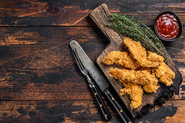Strisce di pollo su un tagliere di legno. fondo di legno scuro. vista dall'alto. copia spazio.