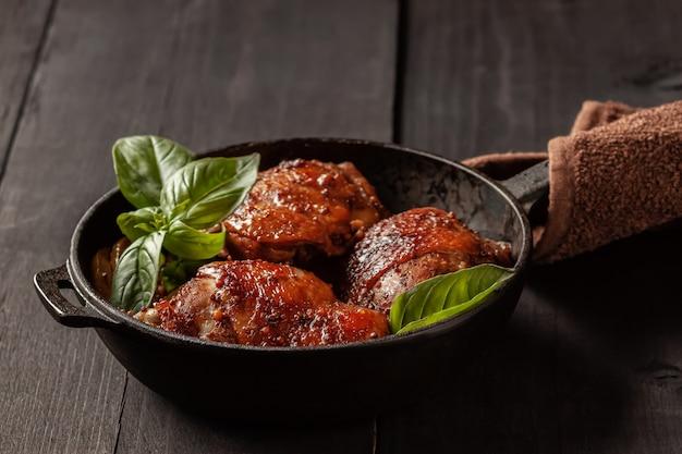 Cosce di pollo e basilico in una padella di ferro nero