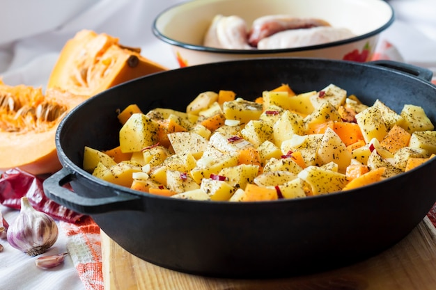 Cosce e cosce di pollo con patate e zucca.