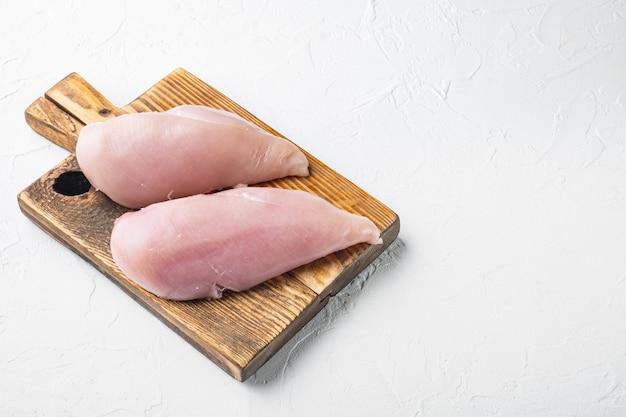 Carne cruda di pollo su priorità bassa bianca con lo spazio della copia
