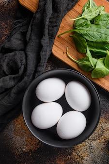 Uova bianche di pollo nella ciotola nera, vista dall'alto.