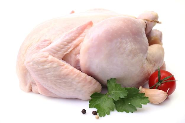Pollo su una superficie bianca con foglie di prezzemolo e pomodoro