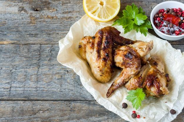 Ali di pollo al forno sulla griglia con erbe fresche, limone sul tavolo di legno.
