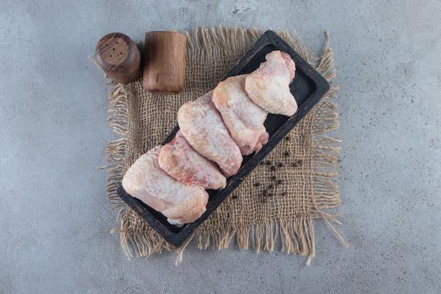 Ali di pollo su una tavola su un tovagliolo di tela, sulla superficie di marmo.
