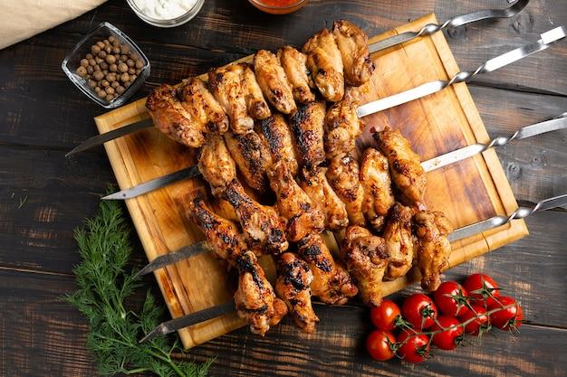 Alette di pollo cotte su spiedini su legno