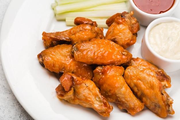 Ali di pollo in salsa su un piatto