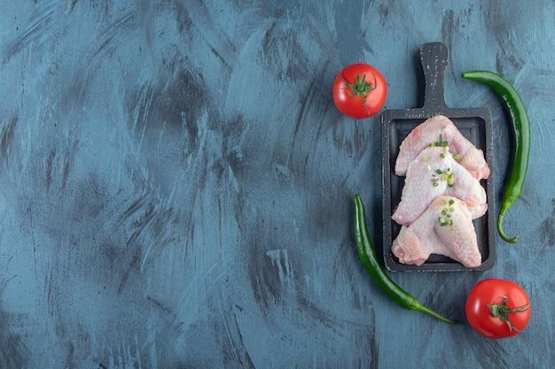 Ali di pollo e verdure su una tavola, sullo sfondo blu.