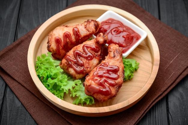 Ali di pollo con ketchup su un tavolo di legno.