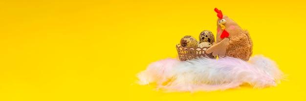 Pollo con uova di pasqua in un cestino. tema di pasqua su sfondo giallo. il pollo giocattolo tiene in mano un cesto di uova. posto per il tuo testo.