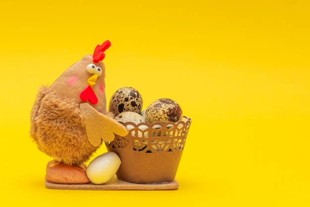 Pollo con uova di pasqua in un cesto tema pasquale su sfondo giallo il pollo giocattolo