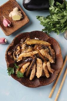 Pollo con melanzane in salsa piccante. spuntino casalingo asiatico delizioso sulla tavola blu-chiaro. vista dall'alto. avvicinamento