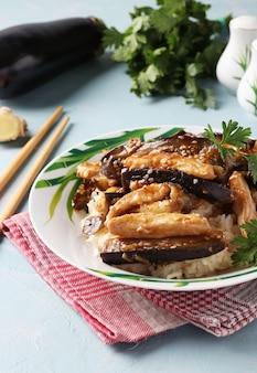Pollo con melanzane in salsa piccante. spuntino casalingo asiatico delizioso sulla tavola blu-chiaro.