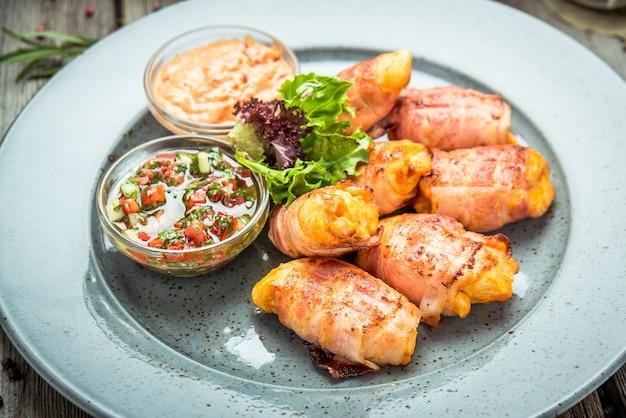 Pollo con pancetta alla griglia, su uno sfondo di legno