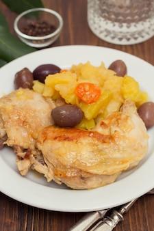 Pollo con la patata e le olive sul piatto bianco su superficie di legno