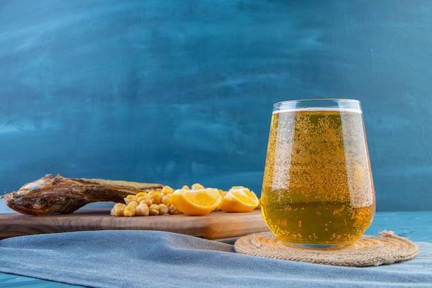 Ceci, fette di limone e pesce essiccato su un tagliere su un canovaccio, sullo sfondo blu.