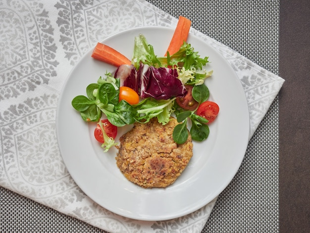 Hamburger vegetariano di ceci e insalata su una piastra bianca su una tovaglia grigia e tovagliolo, vista da sopra