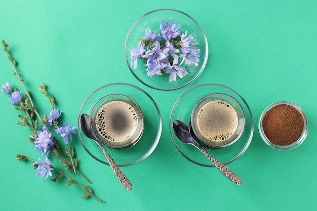 Bevanda di cicoria in due bicchieri di vetro, con concentrato e fiori sul verde