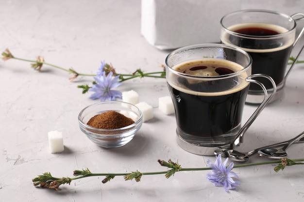 Bevanda di cicoria in due bicchieri di vetro, con concentrato e fiori su fondo grigio. bevanda salutare a base di erbe