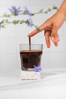 Bevanda di cicoria in tazza trasparente con fiori di cicoria in primo piano