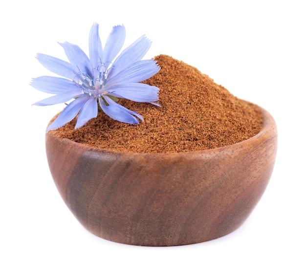 Cicoria in polvere e fiore in ciotola di legno isolato su sfondo bianco cichorium intybus