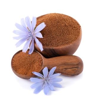 Cicoria in polvere e fiore in ciotola di legno e cucchiaio isolati su sfondo bianco cichorium intybus